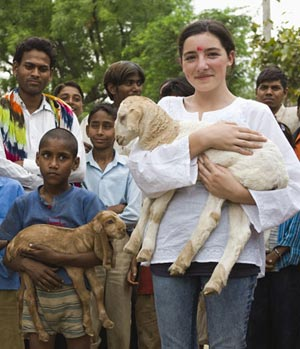 Volunteer poses with lamb and children